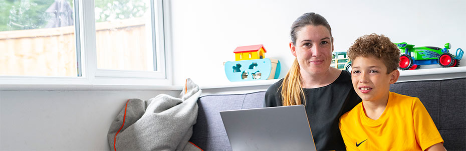 single mum and kid on couch with laptop